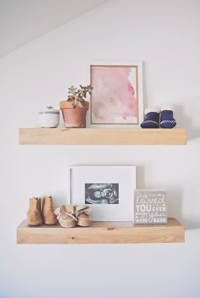 Framed sonogram and baby artwork on shelf